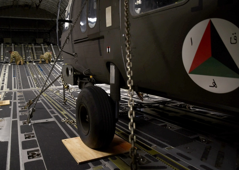 A U.S. Air Force C-17 loadmaster assigned to Charleston Air Force Base, S.C., prepares two Afghan Air Force UH-60 helicopters for unloading Sept. 18, 2017, at Kandahar Air Field, Afghanistan. These are the first UH-60s to be delivered to Afghanistan for the recapitalization of the AAF and development of a professional, capable and sustainable Afghan Air Force. (U.S. Air Force photo by Tech. Sgt. Veronica Pierce)