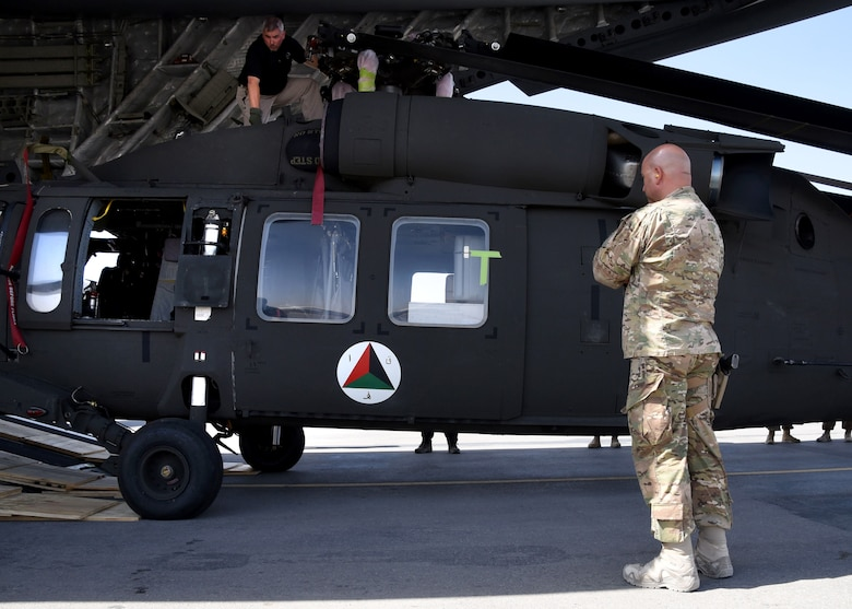 U.S. Air Force Col. Armando Fiterre, the 738th Air Expeditionary Advisory Group commander, Train, Advise, Assist, Command-Air, watches as the first Afghan Air Force UH-60 helicopter is unloaded off a U.S. Air Force C-17 Globemaster, Sept. 18, 2017, at Kandahar Air Field, Afghanistan. The UH-60 arrival is part of the recapitalization efforts of the AAF. The plan involves seven different weapon systems, 14 program offices and more than 20 major contracts. TAAC-Air will oversee training of AAF pilots and maintainers. (U.S. Air Force photo by Tech. Sgt. Veronica Pierce)