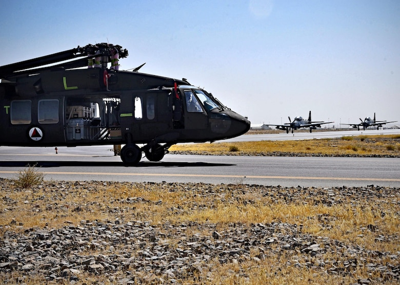 An Afghan Air Force UH-60 is towed as two AAF A-29s taxi for take-off Sept. 18, 2017, at Kandahar Air Field, Afghanistan. The UH-60 was the first to arrive in Afghanistan as part of modernization efforts to transition the AAF to a more sustainable and modern helicopter fleet. (U.S. Air Force photo by Tech. Sgt. Veronica Pierce)