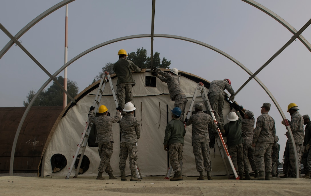 U.S. Airmen assigned to the 786th and 86th Civil Engineer Squadrons pull a portion of fabric for a small shelter system tent over its metal frame during the 86 CEG Prime Base Engineer Emergency Force training day on Ramstein Air Base, Germany, Sept. 21, 2017. Prime BEEF holds a training day once a month to ensure the 86th CEG Airmen are qualified for all requirements needed when they are in austere locations. (U.S. Air Force photo by Senior Airman Tryphena Mayhugh)