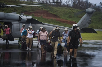 U.S. Sailors with Helicopter Sea Combat Squadron 22, supporting Joint Task Force - Leeward Islands , escort U.S. citizens to the evacuation control center  at Douglas-Charles Airport in Dominica, Sept. 24, 2017