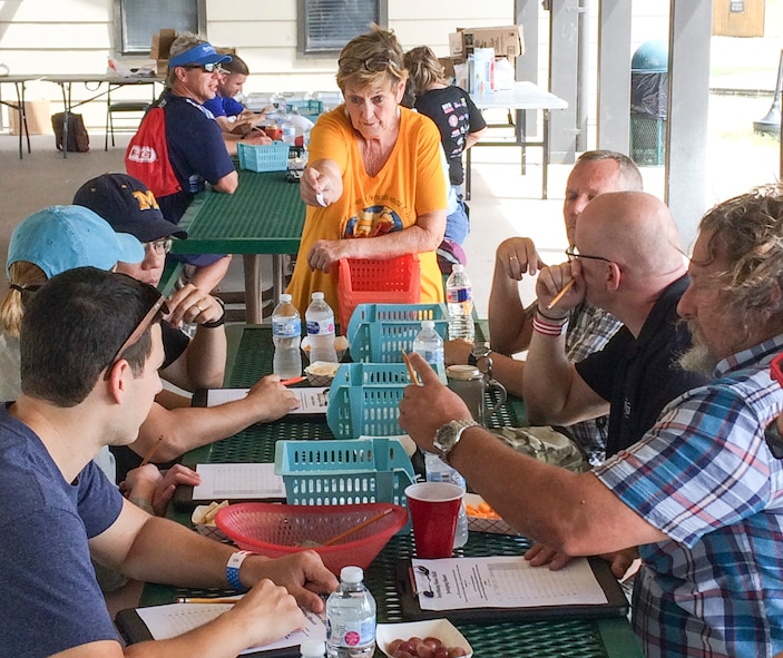 """Laura Coad, Chili Cook-Off coordinator, provides instruction to the judges for the """"Anything Goes"""" category during the Ruckus at the Rec Camp at the Goodfellow Air Force Base Recreation Camp, San Angelo, Texas, Sept. 23, 2017. The competition included categories for teams and individuals in the Terlingua, chicken, ribs, beans and """"anything goes"""" category. (U.S. Air Force photo by Aryn Lockhart/Released)"""