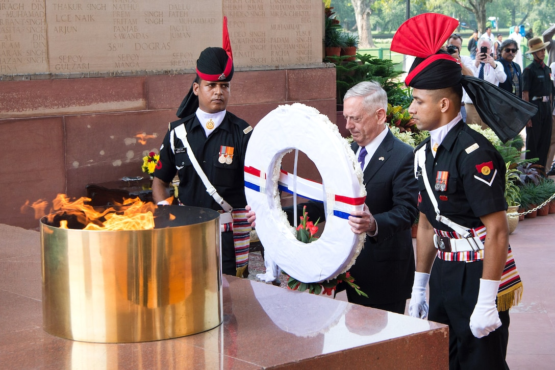 Defense Secretary Jim Mattis, flanked by two Indian service members, holds a wreath while standing before an eternal flame.