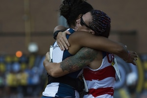 Retired Marine Corps Cpl. Sarah Rudder, right, hugs a French athlete after competing in the women's 100-meter dash.