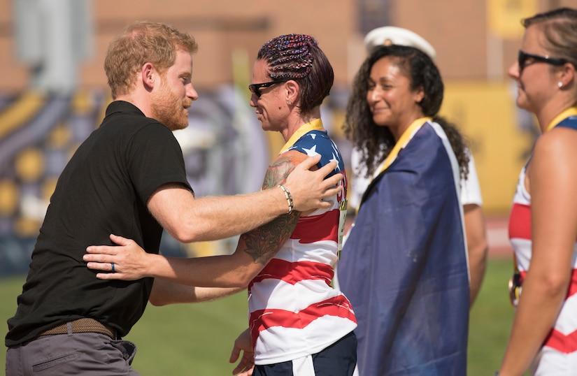 Prince Harry hugs Marine Corps veteran Lance Cpl. Sarah Rudder.