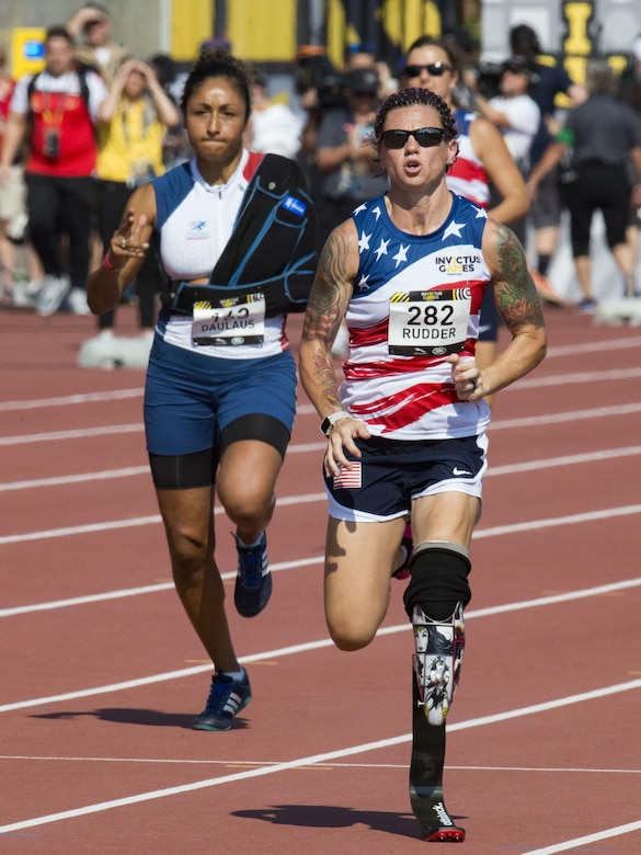 Retired Marine Corps Cpl. Sarah Rudder, right, competes in the women's 100-meter dash.