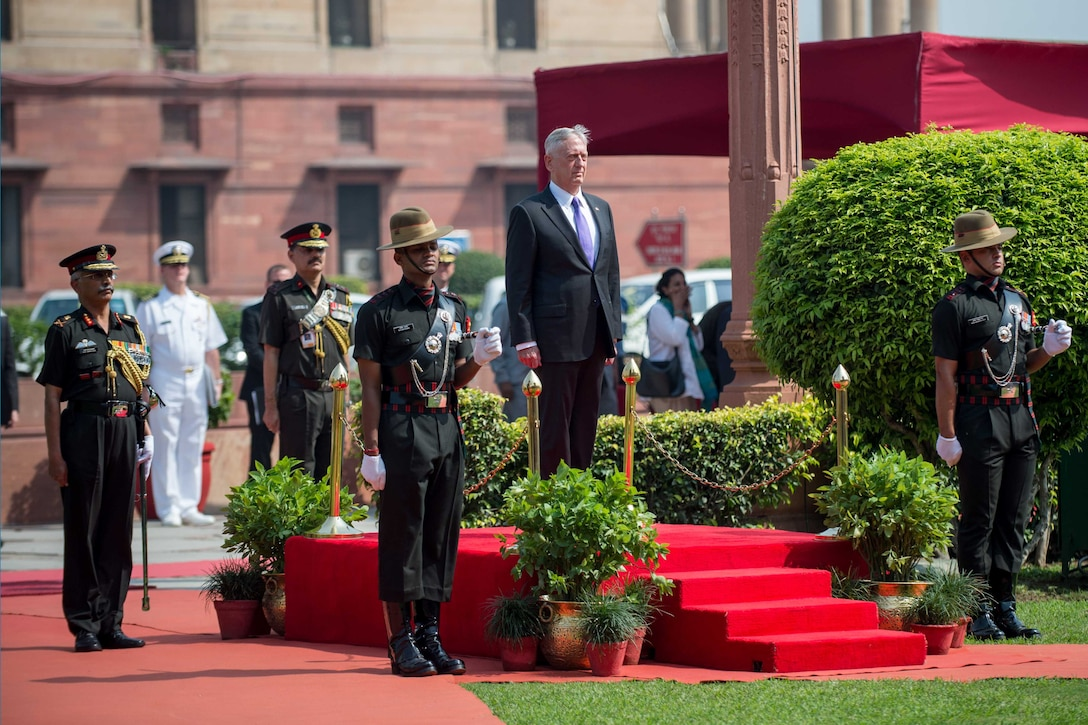 Defense Secretary Jim Mattis stands at attention.
