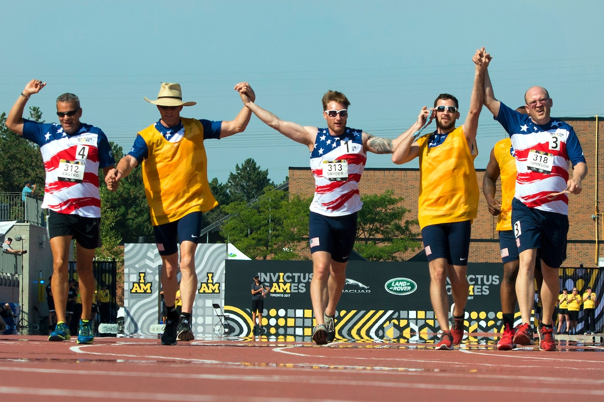 Visually impaired runners join hands to finish their race as a team.