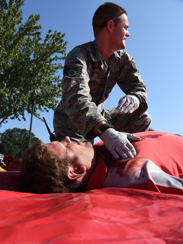 Staff Sgt. Terry Durbin Jr., 81st Medical Operations Squadron emergency services medical technician, medially assesses Samuel Raleigh, 81st Communications Squadron quality assurance inspector, who portrays a victim during an active shooter exercise outside of the Arnold Medical Annex Sept. 21, 2017, on Keesler Air Force Base, Mississippi. An active duty Air Force member simulated opening fire at the Arnold Medical Annex and the Larcher Chapel in order to test the base's ability to respond to and recover from a mass casualty event. (U.S. Air Force photo by Kemberly Groue)