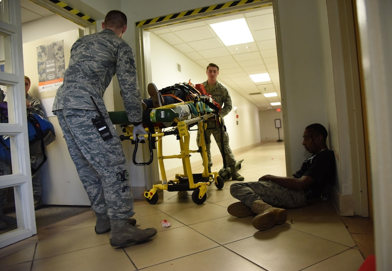 Members of the 81st Medical Group retrieve actors portraying victims from the scene during an active shooter exercise at the Arnold Medical Annex Sept. 21, 2017, on Keesler Air Force Base, Mississippi. An active duty Air Force member simulated opening fire at the Arnold Medical Annex and the Larcher Chapel in order to test the base's ability to respond to and recover from a mass casualty event. (U.S. Air Force photo by Kemberly Groue)