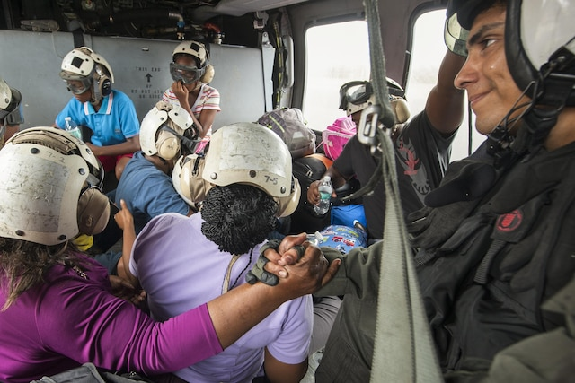 A service member holds hands with an evacuee on an aircraft carrying half a dozen people.