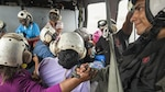 A sailor holds the hand of a hurricane victim during a helicopter ride.