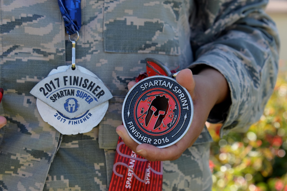 Staff Sgt. Teresa Monteon, 60th Medical Group training manager from San Jose, Calif., displays some of her Reebok Spartan Race medals outside David Grant USAF Medical Center at Travis Air Force Base, Calif., Sept. 22. After a five month battle with cancer, Monteon completed three Spartan races. She plans on running her fourth Spartan race on Sept. 30 in Olympic Valley, Calif. (U.S. Air Force photo by Tech. Sgt. James Hodgman)