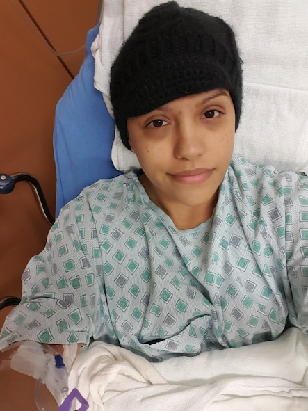Staff Sgt. Teresa Monteon, 60th Medical Group training manager from San Jose, Calif., sits in her hospital bed during a nine-day hospitalization at David Grant USAF Medical Center in December 2016. Monteon was diagnosed with Hodgkin's Lymphoma and is now in remission after undergoing four months of chemotherapy and one month of proton therapy. (Courtesy Photo)