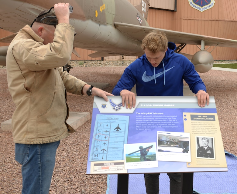 Ryan Ahrenstorff, an eagle scout with Troop 72 from Rapid City, and Master Sgt. Mark Wight, the curator assigned to the South Dakota Air and Space Museum, position a sign in front of an F-100A Super Sabre static display as part of the Adopt-A-Plane Program in Box Elder, S.D., Sept. 23, 2017. Multiple units from Ellsworth Air Force Base and private organizations around the area are adopting aircraft and taking them on as their own by washing, bird proofing and performing minor upkeep. (U.S. Air Force photo by Airman 1st Class Thomas Karol)
