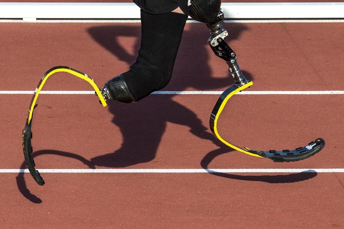 An Army veteran runs with yellow prosthetic legs as his shadow follows.