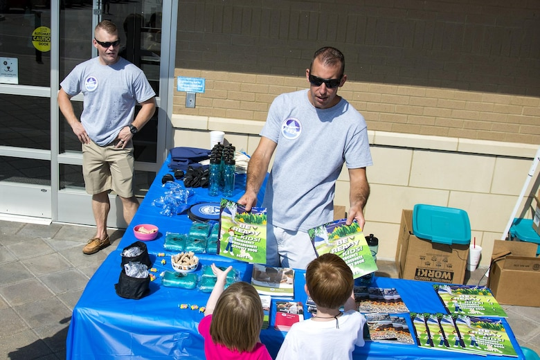Tech. Sgt. Nick Olson, 23d Civil Engineer Squadron emergency management NCO in charge of training and logistics, hands coloring books to children at a local pet store, Sept. 23, 2017, in Valdosta, Ga. Members of the 23d CES hosted the event as part of National Preparedness Month to educate pet owners on disaster precautions. (U.S. Air Force photo by Airman 1st Class Erick Requadt)