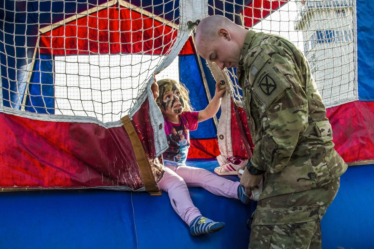 A soldier helps a child put on her shoes.