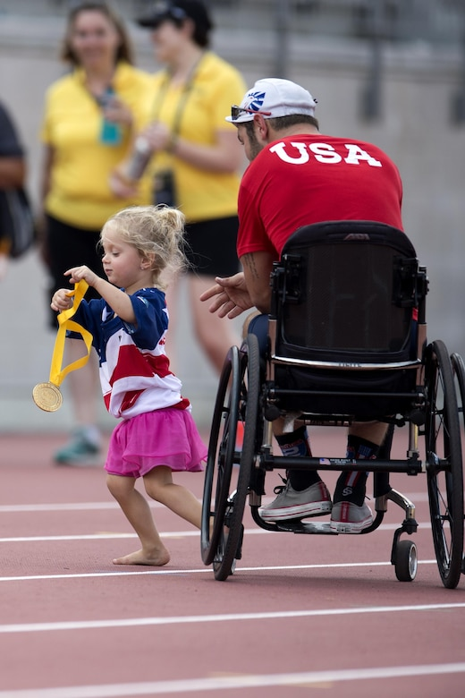 Vada DeWalt, 3, daughter of medically retired Navy Petty Officer 3rd Class Nate DeWalt, right, runs off with her father's gold medal.