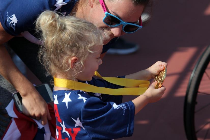 Vada DeWalt, 3, daughter of medically retired Navy Petty Officer 3rd Class Nate DeWalt, shows her mom, Erica, her dad's gold medal