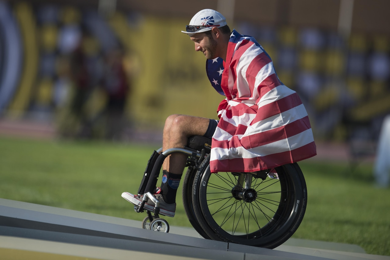 Medically retired Navy Petty Officer 3rd Class Nate DeWalt takes the medals stage to receive a gold medal in wheelchair racing.
