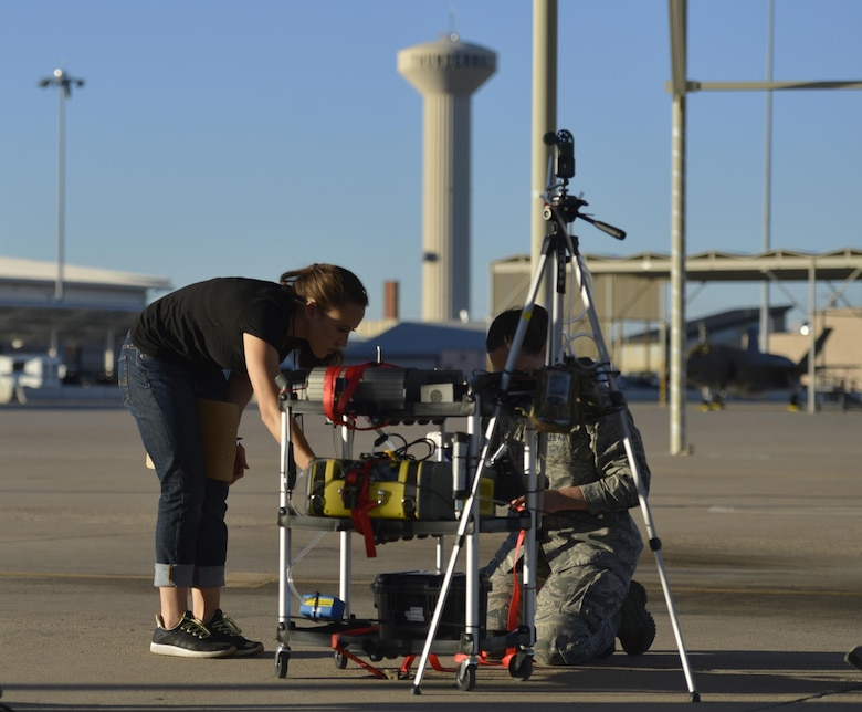 Danielle McKenzie-Smith, USAF School of Aerospace Medicine bioenvironmental engineer secures testing equipment on the flightline at Luke Air Force Base, Ariz., Sept. 20, 2017. McKenzie-Smith and the team strategically placed equipment to test chemicals, particle sizes and the distribution of particles in the air related  to the F-35A Lightning II program.  (U.S. Air Force photo/Airman 1st Class Caleb Worpel)