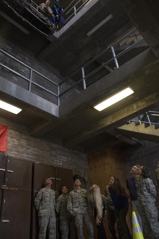 Members of the senior leader's immersion tour watch as firefighter trainees practice lowering a victim at the Louis F. Garland Department of Defense Fire Academy at Goodfellow Air Force Base, Texas, Sept. 25, 2017. The tour of the fire academy included planes and buildings that are used to train Goodfellow's future firefighters. (U.S. Air Force photo by Airman Zachary Chapman)