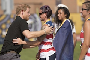 Prince Harry hugs an athlete as others watch.