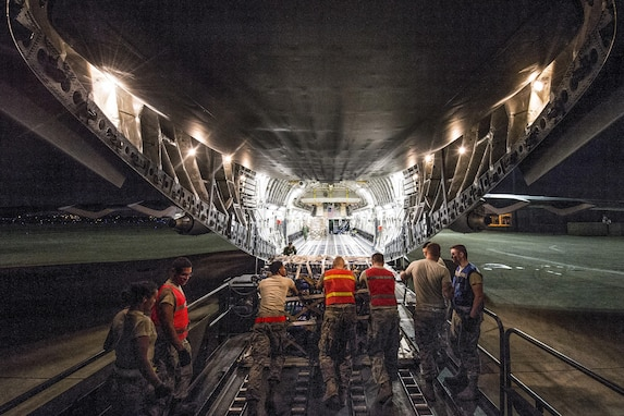 Airmen load palletized food and water onto an aircraft at night.