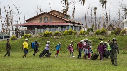 A sailor leads residents with suitcases to a helicopter for evacuation.