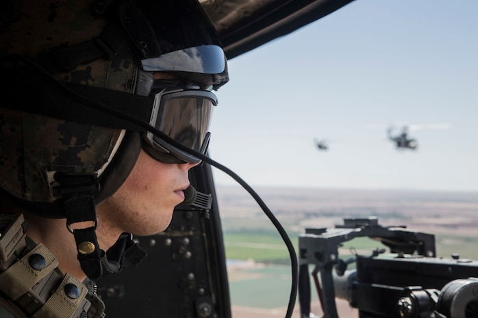 U.S. Marine Corps Cpl. Christopher Madere, crew chief, with Marine Light Attack Helicopter Squadron 469 (HMLA-469) assess targets during an aerial gunnery refinement drill in support of Weapons and Tactics Instructor course (WTI) 1-18 at Chocolate Mountain, Aerial Gunnery Range, Calif., Sept 25, 2017. WTI is a seven week training event hosted by Marine Aviation Weapons and Tactics Squadron One (MAWTS-1) cadre which emphasizes operational integration of the six functions of Marine Corps Aviation in support of a Marine Air Ground Task Force and provides standardized advanced tactical training and certification of unit instructor qualifications to support Marine Aviation Training and Readiness and assists in developing and employing aviation weapons and tactics. (U.S. Marine Corps photo by Sgt. Allison Lotz)