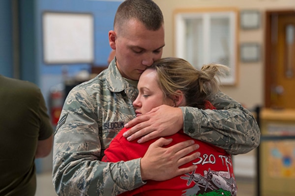A male service member hugs a female family member.