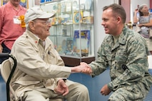 Col. Walt Jackim, 45th Space Wing vice commander, receives a coin from Frank Losonsky, the sole remaining member of the American Volunteer Group Flying Tigers during a visit to Cape Canaveral Air Force Station, Fla. on Sept. 21, 2017. Losonsky and 50 descendants of the original members, toured the Cape and learned how the Flying Tigers and the 45th Space Wing share a distinct lineage as subordinate units of the 14th Air Force. From P-40 Warhawk aircraft to launching rockets into space, 14th Air Force units have been breaking barriers for many decades.