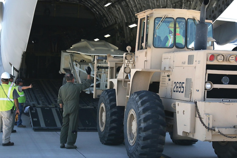 Chief Master Sgt. Jason LeMaster, 89th Airlift Squadron loadmaster, spots a forklift being loaded into the cargo area of a 445th Airlift Wing C-17 Globemaster III aircraft at Biggs Army Field in El Paso, Texas, for transport to aid in Hurricane Harvey relief efforts Aug. 30, 2017. (U.S. Air Force photo/Master Sgt. Patrick O'Reilly)