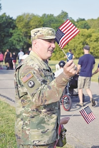 Command Chaplain Shay Worthy of 1st Combat Aviation Brigade, 1st Infantry Division patriotically cheers on his fellow comrades as they run or walk during the 2-mile course during the 5th Annual Fallen Hero Run Sept. 9. The fun run was held by volunteers of DFMWR and Survivor Outreach Services.