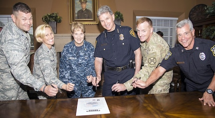 (From left) Col. Thomas Miner, commander, 502nd Security and Readiness Group; Brig. Gen. Heather Pringle, commander, 502nd Air Base Wing and Joint Base San Antonio; Rear Adm. Rebecca McCormick-Boyle, commander, Navy Medicine Education and Training Command; Chief William McManus, chief, San Antonio Police Department; Col. David Raugh, commander, 502nd Force Support Group; and Mark Allen, director, 502nd Security Forces Squadron, prepare to sign the proclamation Sept. 26 for the National Night Out celebration planned at all JBSA locations for Oct. 3.