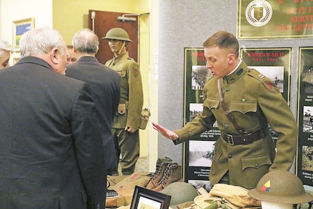 Capt. Robert Cogan, Headquarters and Headquarters Company, 2nd Armored Brigade Combat Team, 1st Infantry Division, explains several World War I artifacts on display at the Officers of the 1st Infantry Division annual dinner at Geary County Convention Center, Junction City, Kansas, April 29. The purpose of the dinner was to allow current and veterans officers of 1st Inf. Div. to socialize with one another and discuss 1st Inf. Div. history and their experiences.