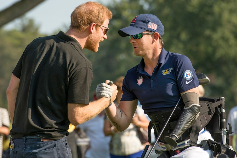 Marine Corps veteran Sgt. Michael Nicholson is congratulated by Britain's Prince Harry after a remarkable drive on the 16th tee.
