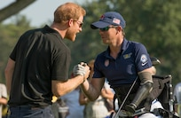 Marine Corps veteran Sgt. Michael Nicholson is congratulated by Prince Harry after a remarkable drive on the 16th tee while competing in Golf at St. George's Golf and Country Club during the 2017 Invictus Games in Toronto on September 26, 2017. The Invictus Games, established by Prince Harry in 2014, brings together wounded and injured veterans from 17 nations for 12 adaptive sporting events, including track and field, wheelchair basketball, wheelchair rugby, swimming, sitting volleyball, and new to the 2017 games, golf.    (DoD photo by Roger L. Wollenberg)