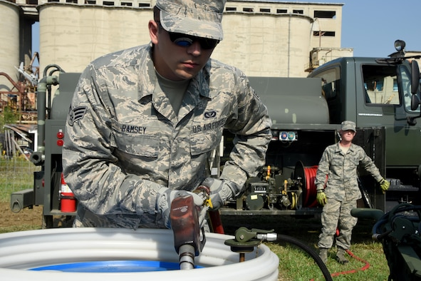 Senior Airman John Ramsey VI loads fuel into a barrel to power a generator as Staff Sgt. Levi Wiskirchen, both from the 269th Combat Communications Squadron, Springfield Air National Guard base, regulates the flow of diesel fuel at the Tech Warrior 2017 exercise, at the National Center for Medical Readiness, Fairborn, Ohio Sept. 21, 2017. The 269 CBCS provided power, air conditioning and land mobile radio support for the 10-day exercise