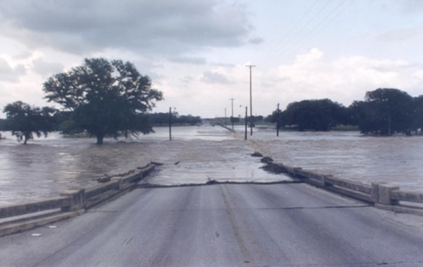"Floodwaters flow across Kelly Street during a heavy downpour at Joint Base San Antonio-Lackland in 2012. Authorities at all base communities monitored weather conditions 24-hours a day and were ready to put up barriers and ""Street Closed"" signs to prevent motorists from crossing the affected areas."