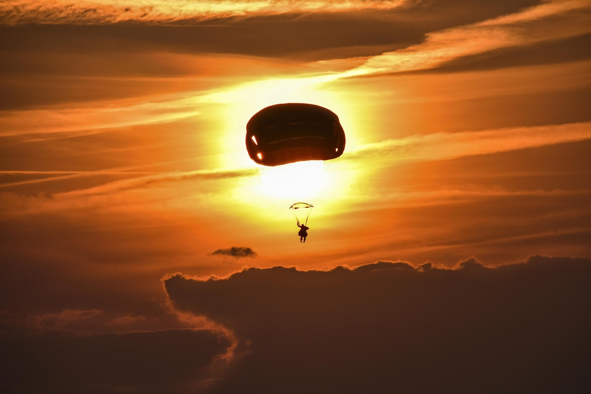 A soldier, shown in silhouette, parachutes toward the ground against an orange sky.