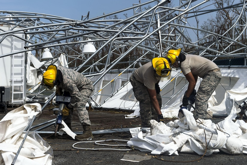 Troops in hard hats clean up debris on the ground near mangled metal structures.