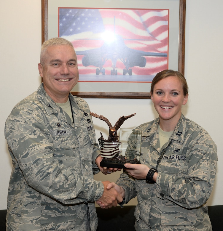 Capt. Lacey Koelling, officer in charge of the 34th Aircraft Maintenance Unit, and Col. Bernard J. Hatch III, the commander of the 28th Maintenance Group, hold the General Lew Allen, Jr., Trophy which was presented to Koelling at Ellsworth Air Force Base, S.D., Sept. 26, 2017. Koelling earned the award for her actions during her deployment to Al-Dhafra Air Base in the United Arab Emirates. (U.S. Air Force photo by Airman 1st Class Thomas Karol)