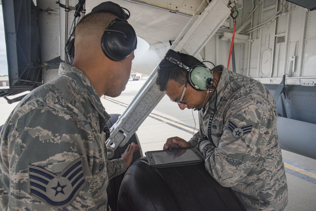 Staff Sergeant Jonathan Carmona, crew chief, reviews a technical order with Senior Airman Jonathan Palascios-Conde, crew chief, on the 108th Wing flightline at Joint Base McGuire-Dix-Lakehurst, N.J., Sept. 20, 2017. Senior Airman Palascios-Conde and Staff Sgt. Carmona, are refueling a KC-135 prior to takeoff. (U.S. Air National Guard photo by Staff Sgt. Ross A. Whitley/Released)