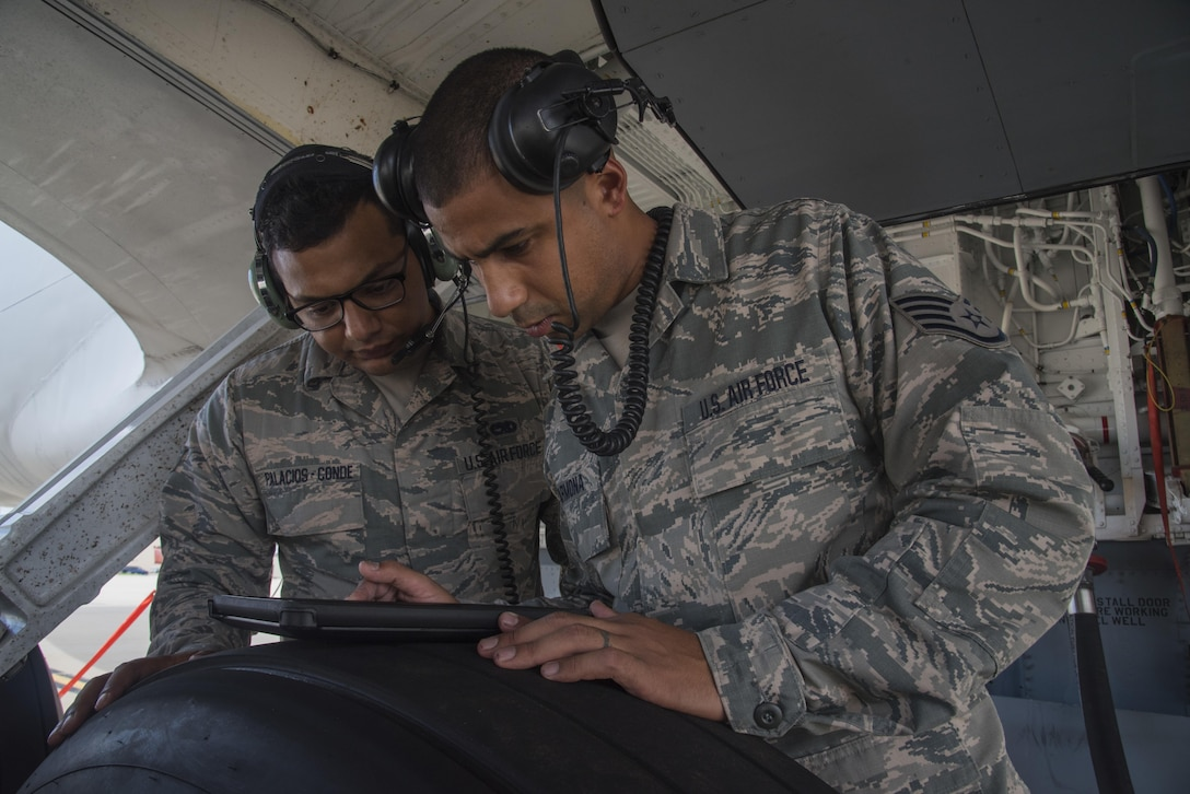 Staff Sergeant Jonathan Carmona, crew chief (right), reviews a technical order with Senior Airman Jonathan Palascios-Conde, crew chief (left), on the 108th Wing flightline at Joint Base McGuire-Dix-Lakehurst, N.J., Sept. 20, 2017. The maintainers, are refueling a KC-135 in preparation of an upcoming mission. (U.S. Air National Guard photo by Staff Sgt. Ross A. Whitley/Released)