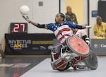Anthony McDaniel, a Marine Corps veteran, reaches for a ball during a wheelchair rugby game against Italy during the 2017 Invictus Games