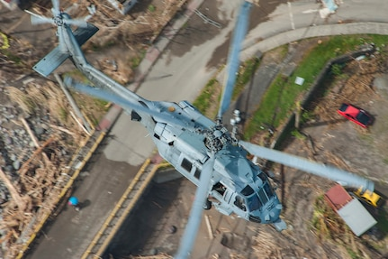 An MH-60S Sea Hawk helicopter flies over the island of Dominica during U.S. citizen evacuations and humanitarian relief following the landfall of Hurricane Maria.