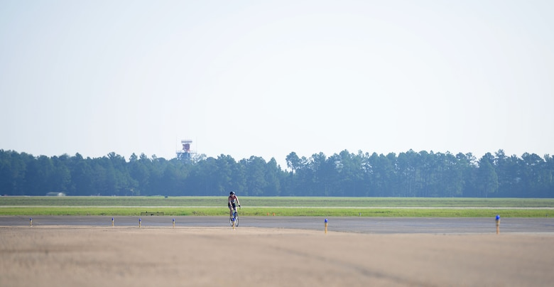 Second Lt. Brooke Cecil, 14th Comptroller Squadron Financial Services Flight Commander, bikes during the base triathlon Sept. 23, 2017, on Columbus Air Force Base, Mississippi. This is one of the few events where BLAZE members will be able to bike down the entire center runway, and shows members who aren't pilots what the flightline looks like. (U.S. Air Force photo by Airman 1st Class Keith Holcomb)