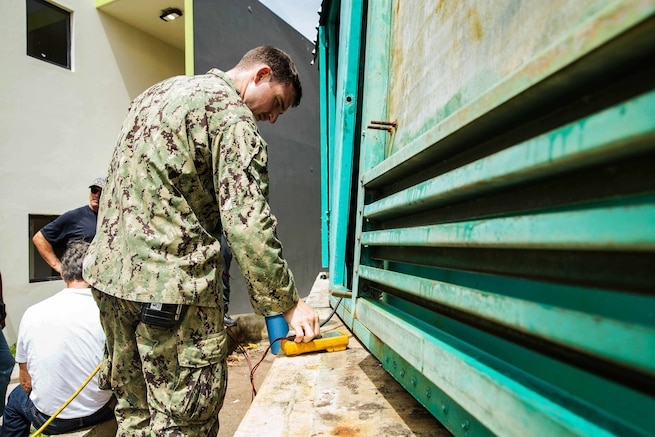 Seaman works on fixing faulty generator.